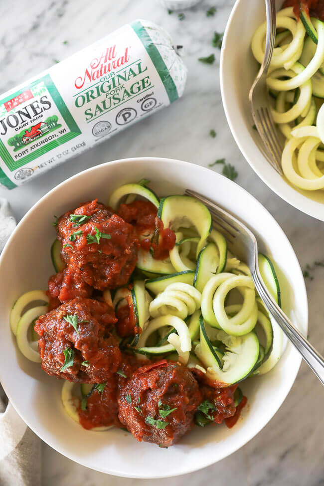 Close up of Italian meatballs served in a bowl over zoodles with a fork dug in.