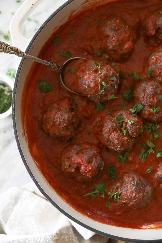 Italian meatballs in marinara sauce in a skillet with a serving spoon scooping up a meatball.