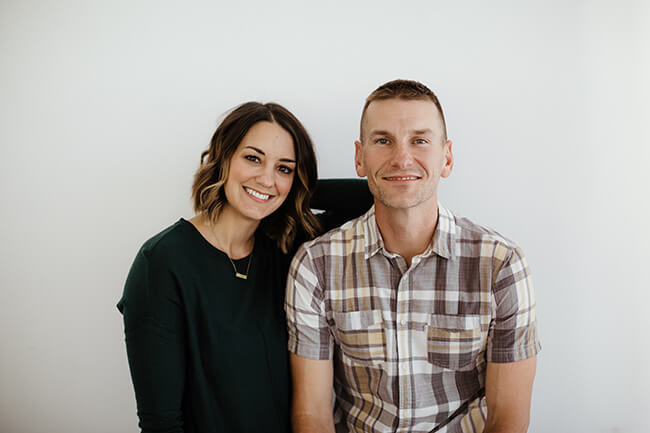 Horizontal image of Justin and Erica Winn against a white wall standing close and smiling.