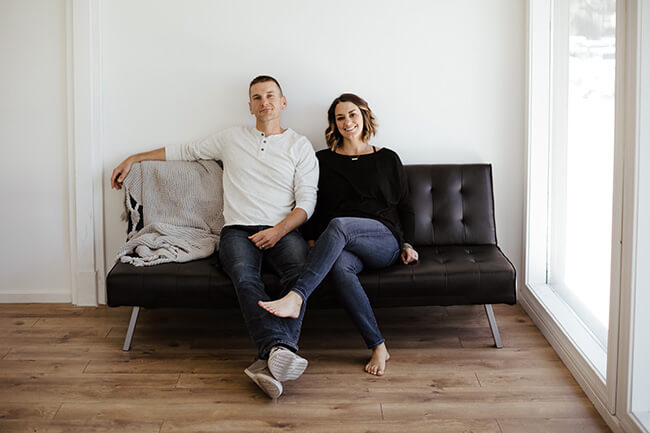 Horizontal image of Justin and Erica Winn sitting on black couch.