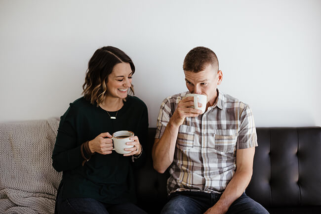 Horizontal image of Justin and Erica Winn drinking coffee on a couch.