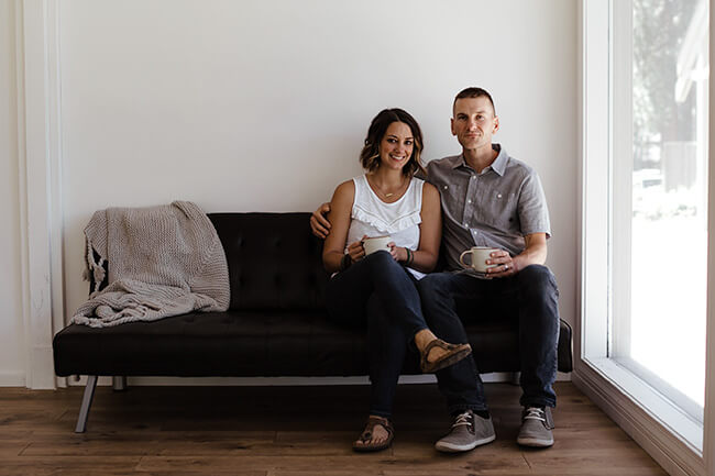Justin and Erica Winn sitting on black couch with coffee cups horizontal image