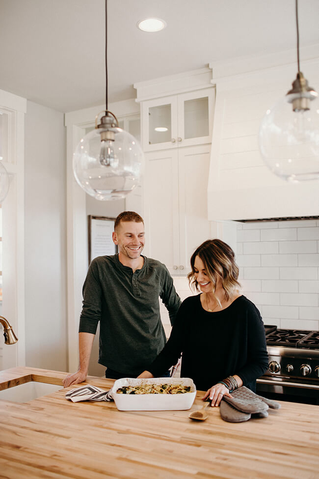 Image of Justin and Erica Winn in the kitchen with a casserole at the counter.