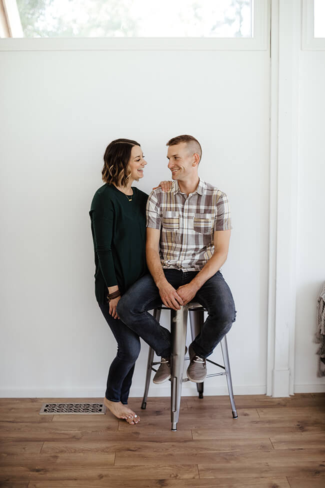 Vertical image of Justin and Erica Winn with Justin sitting on a stool and Erica with her arm on his shoulder. They're smiling at each other.