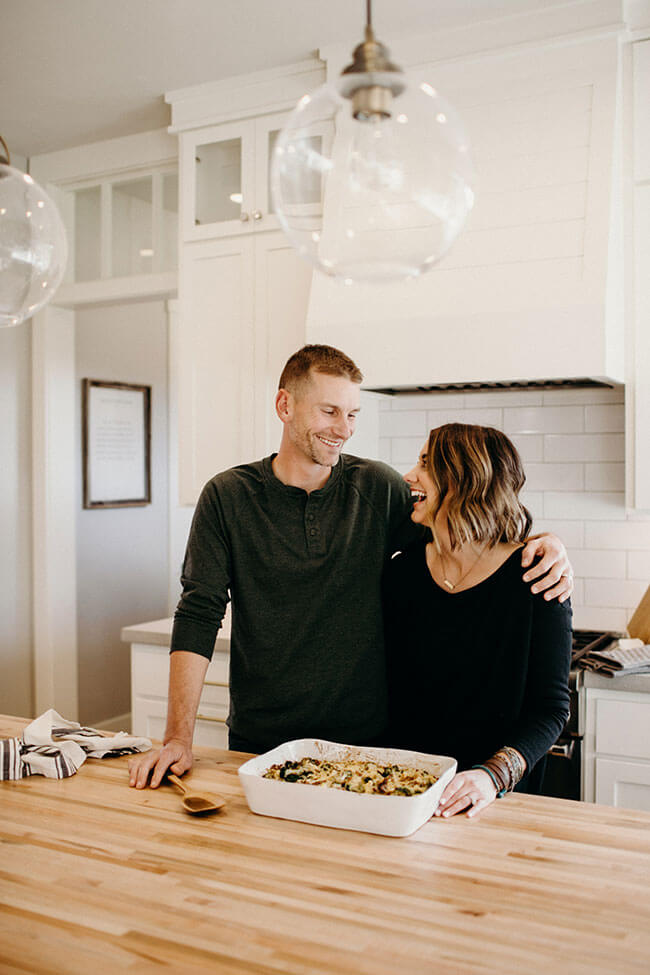 Justin + Erica Winn standing at kitchen counter with casserole dish smiling at each other