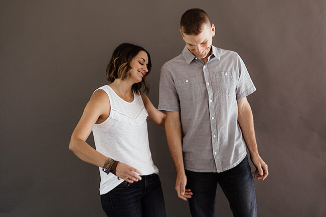 Justin + Erica Winn dancing in front of a gray background horizontal image