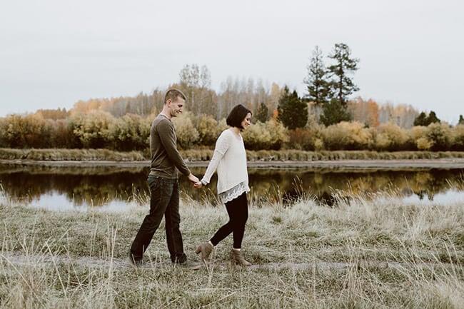 Justin + Erica Winn walking outside in a line holding hands horizontal image