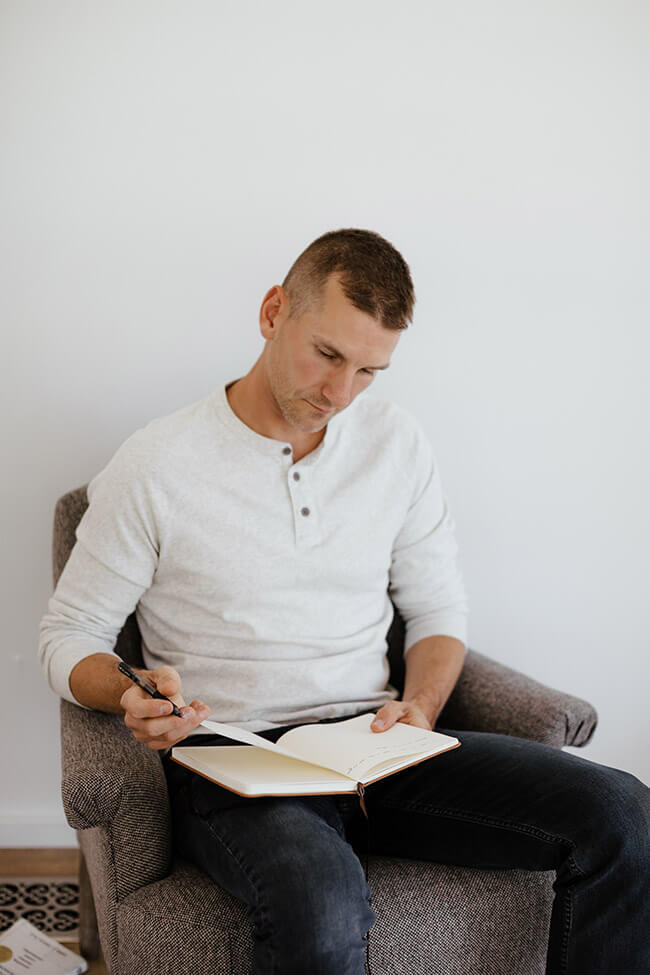 Man on chair with journal writing vertical image