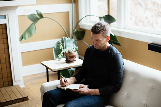 Justin Winn sitting on white couch journaling