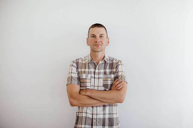 Justin Winn standing with arms crossed horizontal image