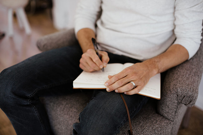 Man on chair with journal writing horizontal image close up