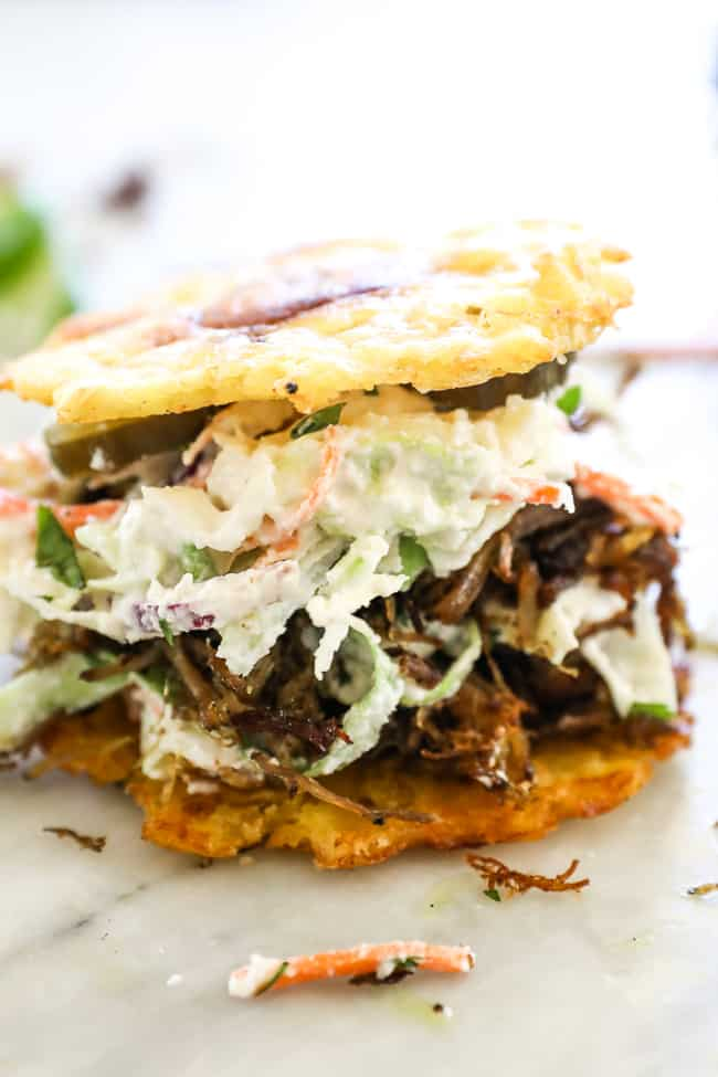 Straight on shot of jibarito with plantain buns, pulled pork, slaw and pickles.
