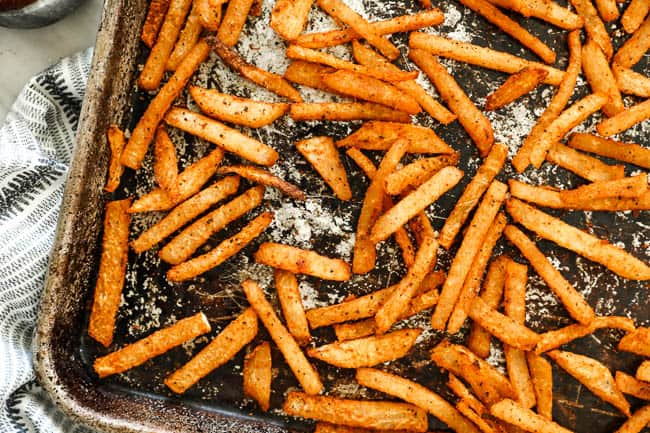 Horizontal overhead image of jicama fries spread out on a sheet pan.