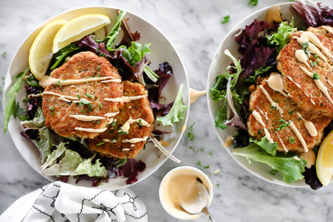 Horizontal overhead image of salmon patties on a plate served over fresh greens and topped with drizzle of spicy aioli sauce.