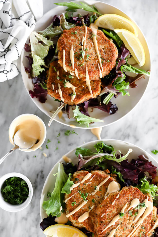 Vertical overhead image of two plates with two salmon patties on each plate served over fresh greens and drizzled with spicy aioli sauce. Extra sauce and chopped parsley on the side.