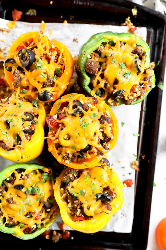 Stuffed bell peppers topped with melted cheddar cheese on a sheet pan