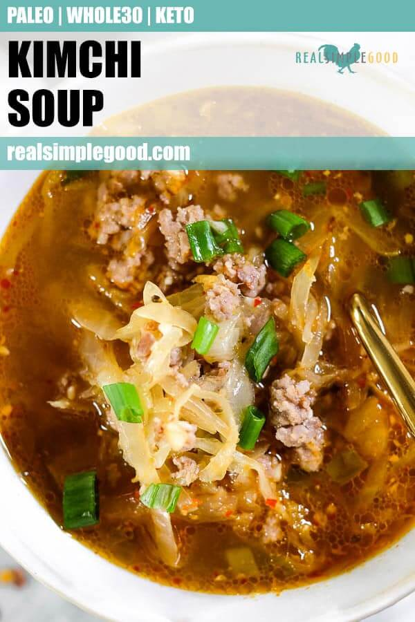 Close of of bowl of kimchi soup topped with chopped green onion for long pinterest pin.