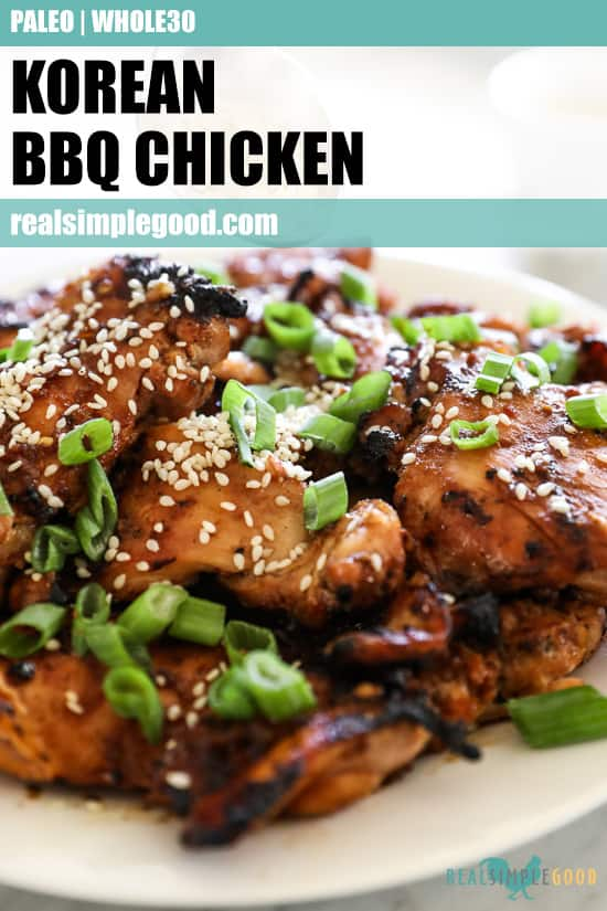 Close up angled shot of Korean bbq chicken stacked on a plate with sliced green onion and sesame seeds on top. Text over at top for pinterest.