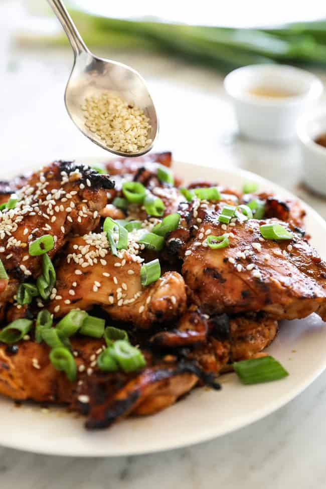 Korean BBQ chicken stacked on a plate with spoon of sesame seeds coming in.