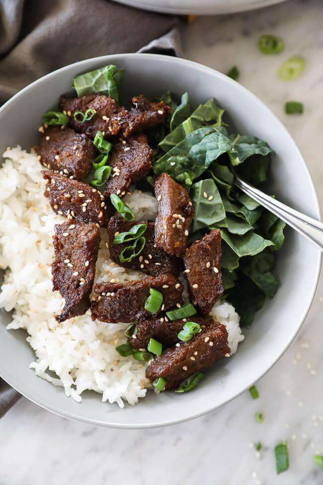 Korean beef bulgogi in a bowl with kale and rice close up vertical image