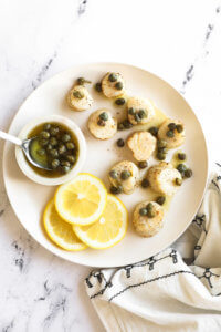 Lemon butter air fryer scallops on a white plate with butter sauce and capers on top. Lemon slices and capers in the side.