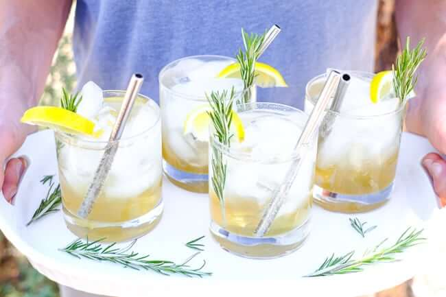 Holding a tray with four glasses of iced lemon & rosemary cocktail with lemon wedges, fresh rosemary and stainless steel straws.