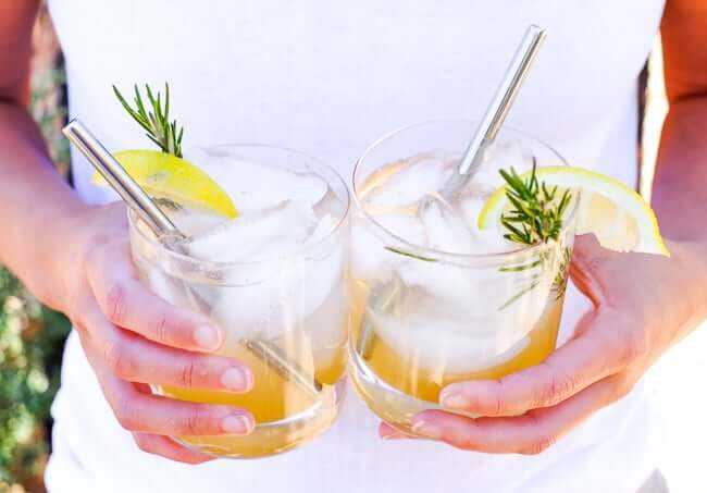 Holding two glasses of this lemon & rosemary cocktail with stainless steel straws in glasses.