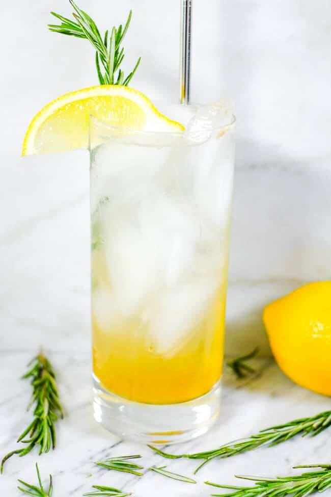 Tall glass of iced lemon & rosemary cocktail with lemon wedge and fresh rosemary garnish.