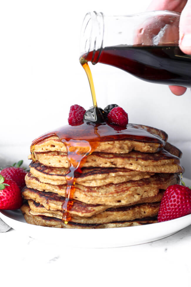 Stack of gluten free pancakes with maple syrup being poured on top and dripping down the side of the stack.