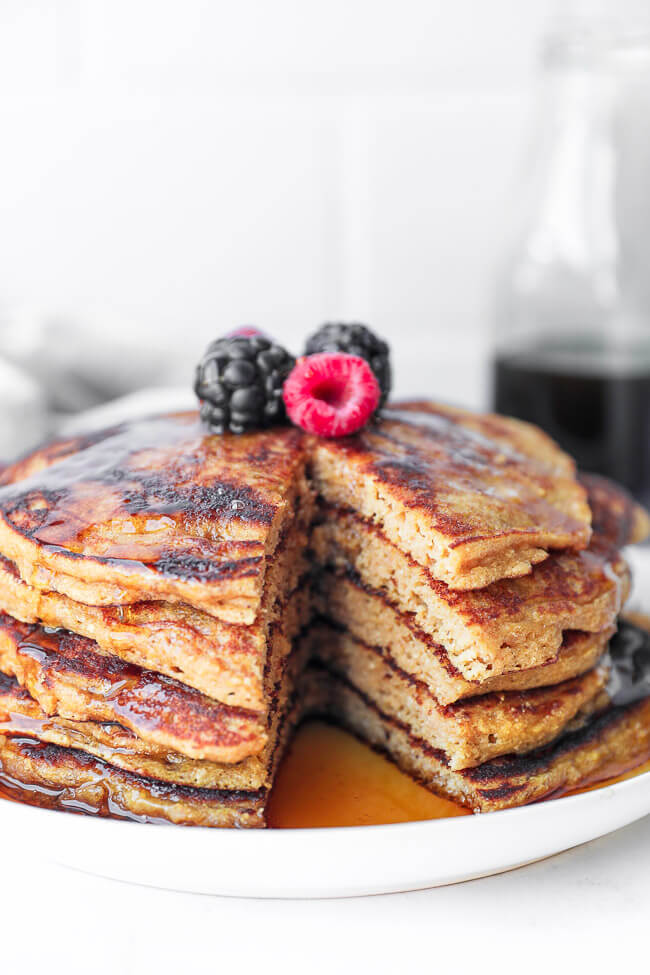 Stack of gluten free pancakes on a plate with a bite cut out and maple syrup drizzled on top. Also topped with raspberries and blackberries.