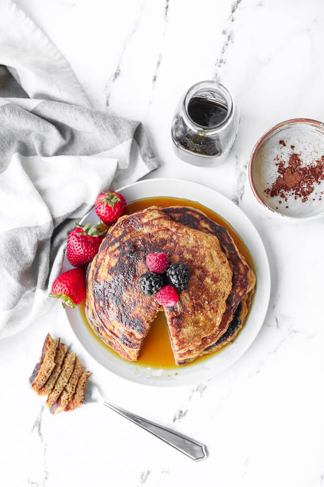 Overhead image of stack of vegan pancakes with a bite cut out. Berries on top with maple syrup drizzled on top. Extra syrup and a mug of coffee on the side.