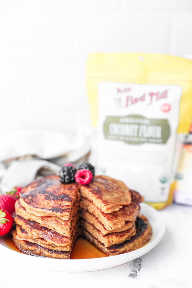 Straight on image of stack of gluten free pancakes with berries on top and a big bite cut out of the stack.