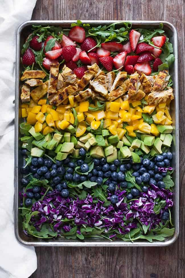 Salad on a sheet pan with ingredients in rows. Strawberries, chicken, bell pepper, avocado, blueberry, cabbage