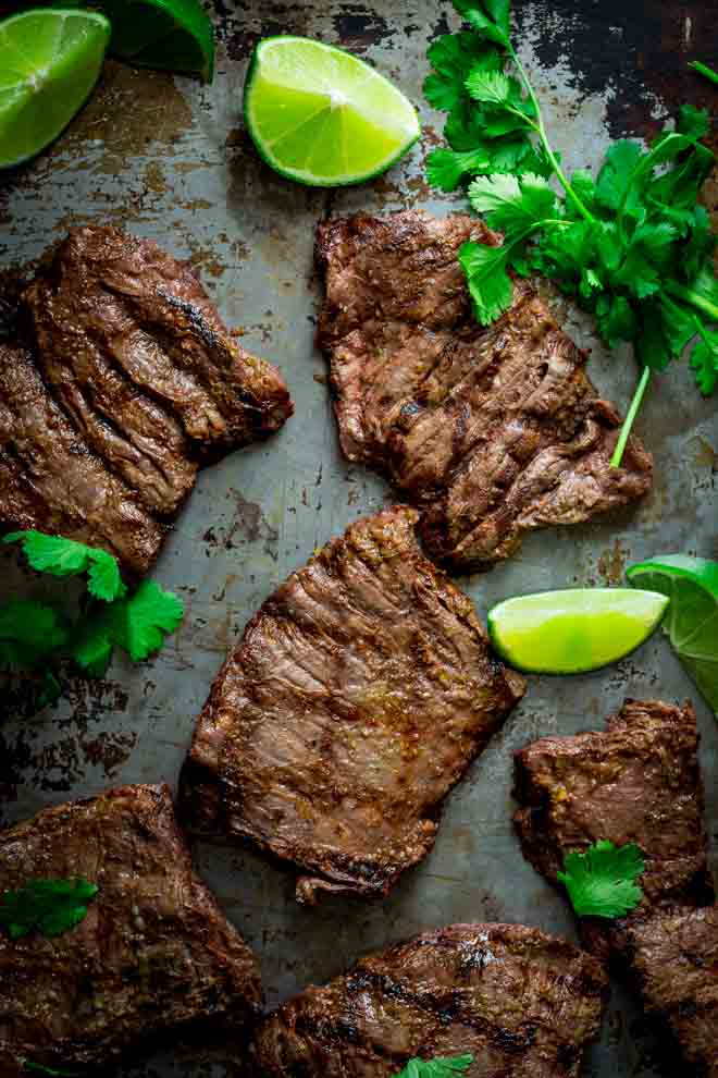 Grilled skirt steak on a sheet pan with cilantro and lime
