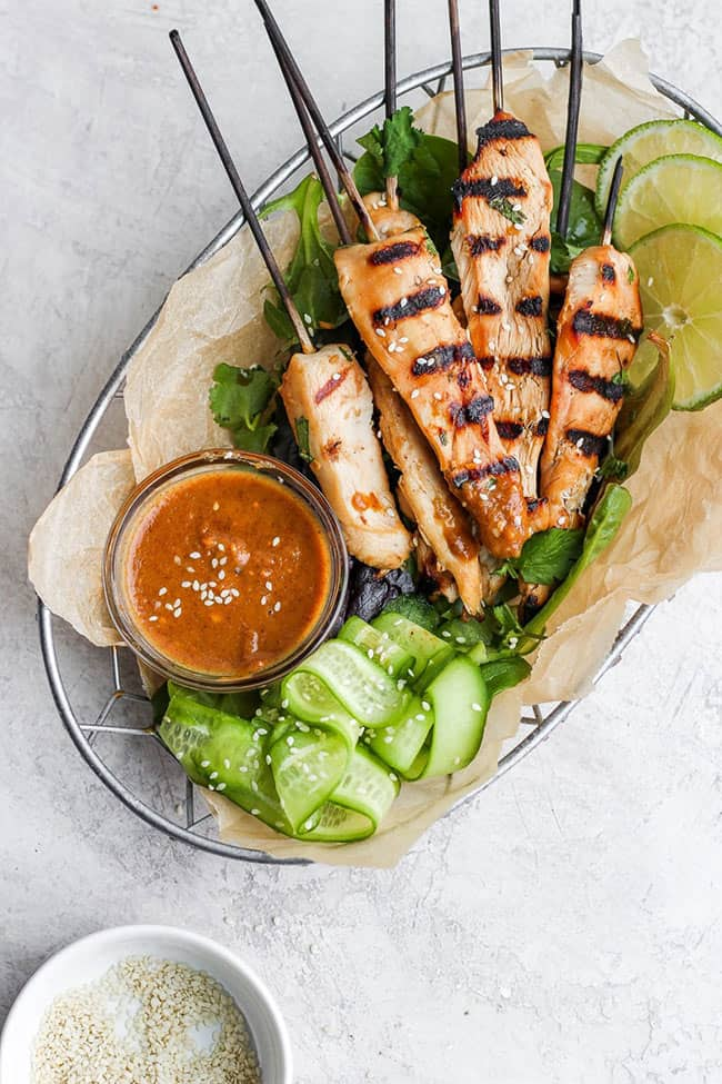 Chicken skewers in a basket with cucumbers and orange sauce