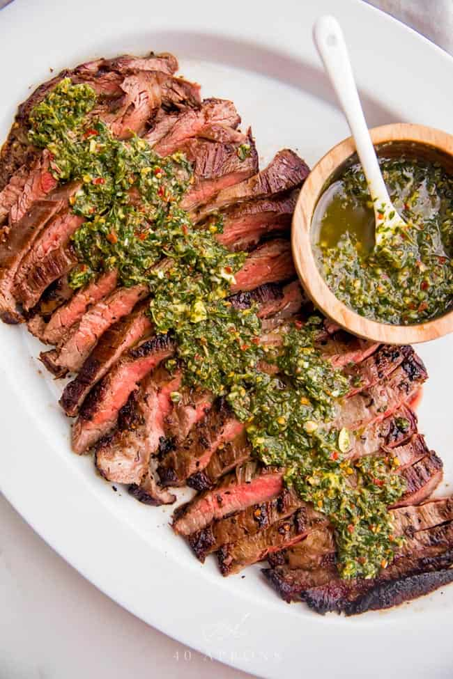 Flank steak slices on a plate with chimichurri sauce on top