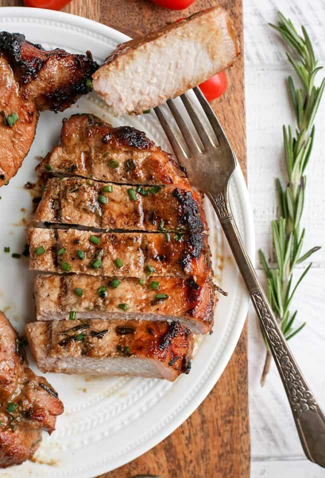 Grilled pork chops sliced on a plate with fork holding one slice