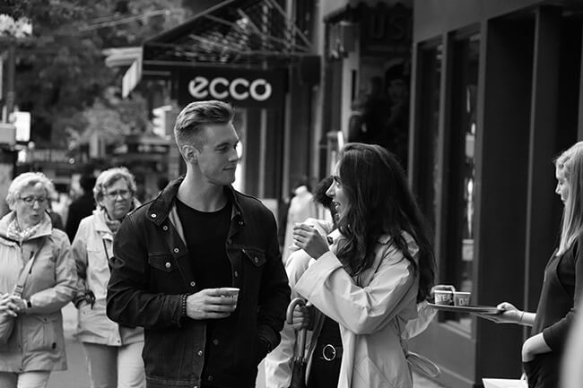 Man and woman on street with cups looking at each other