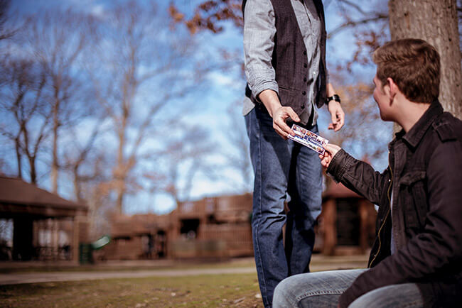 Man handing another man a postcard in a park