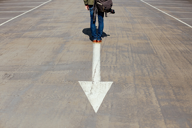 Man standing on runway with arrow pointing down