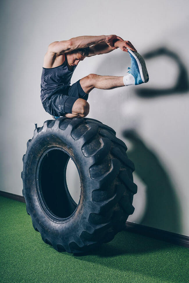 Man stretching on top of a large tire