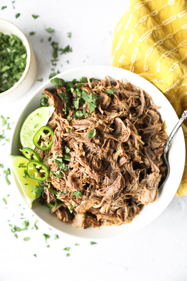 Shredded marinated instant pot mojo pulled pork in a white bowl with lime, cilantro and jalapeno garnish