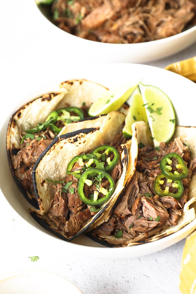Angled image of three shredded pork tacos with sliced jalapeños and chopped cilantro on top.