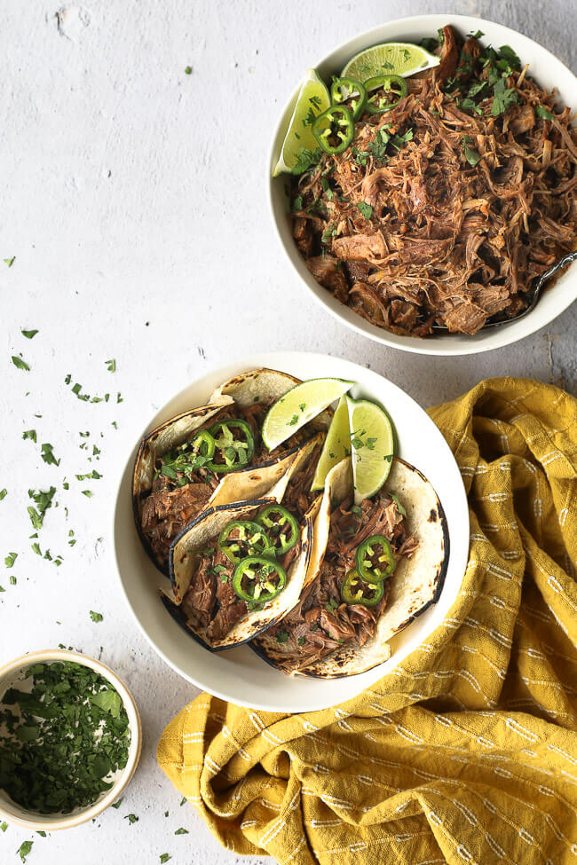 A bowl of shredded mojo pork with some used to make three tacos served up in a dish with lime wedges, chopped cilantro and sliced jalapeño.