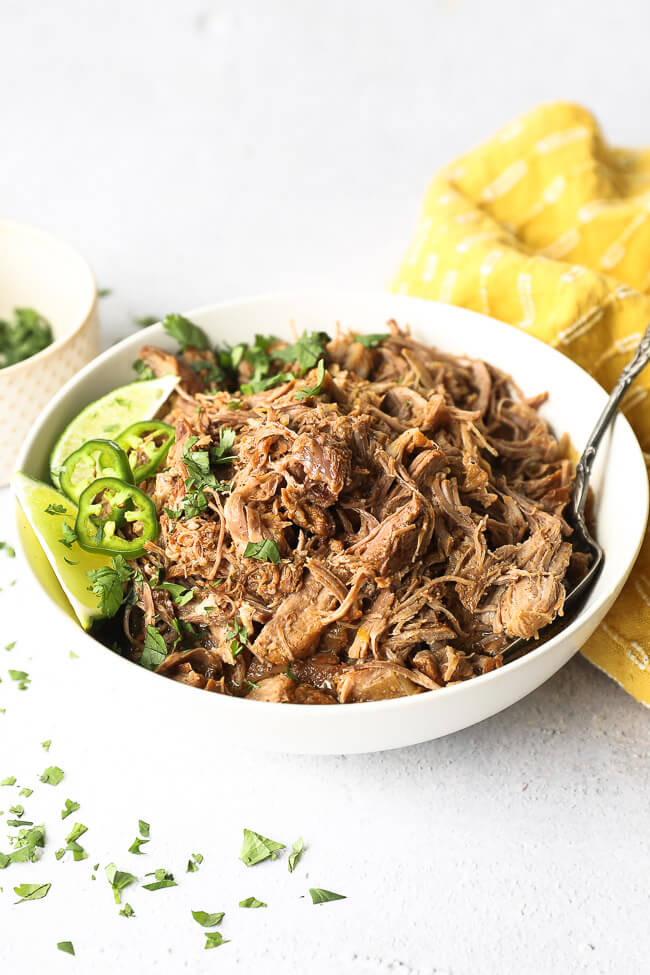 Angled image of marinated mojo pork shredded in a bowl with a serving spoon. Topped with lime wedges, chopped cilantro and sliced jalapeño.