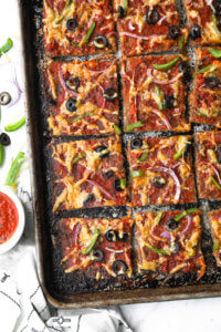 Meatza (or meatzza) pizza on a sheet pan cut into squares (overhead image)
