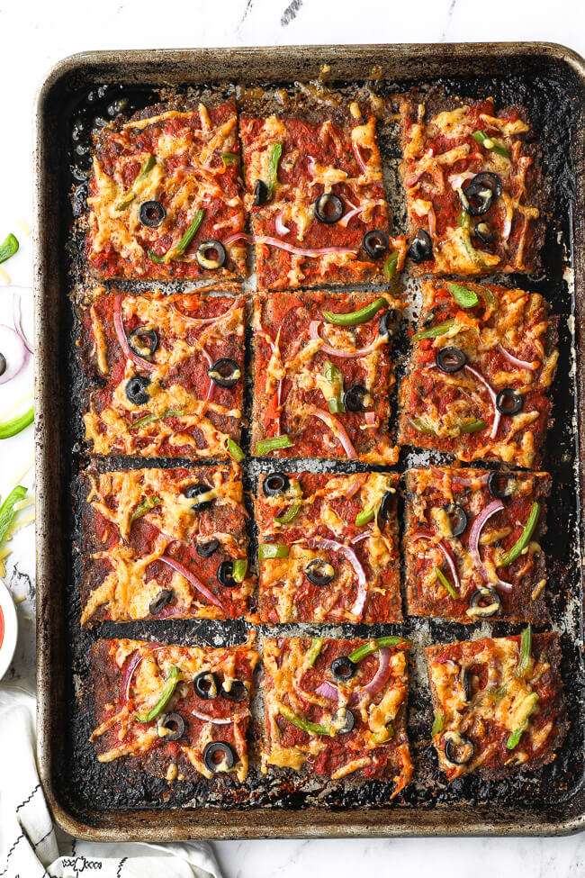 Overhead shot of sheet pan of meat pizza sliced into squares with cheese, olive, bell pepper and red onion topping