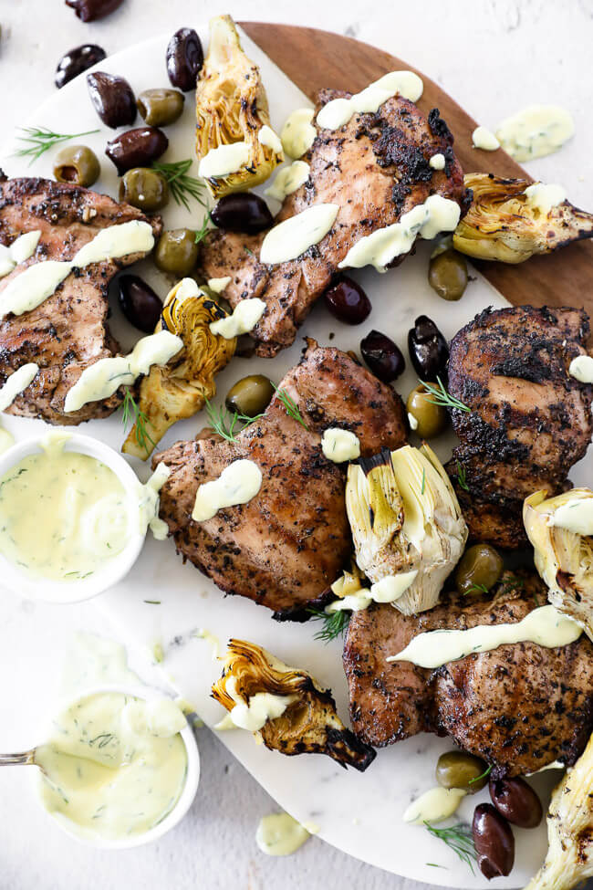 Overhead image of grilled mediterranean chicken on a platter with sauce drizzle, artichoke hearts and olives.