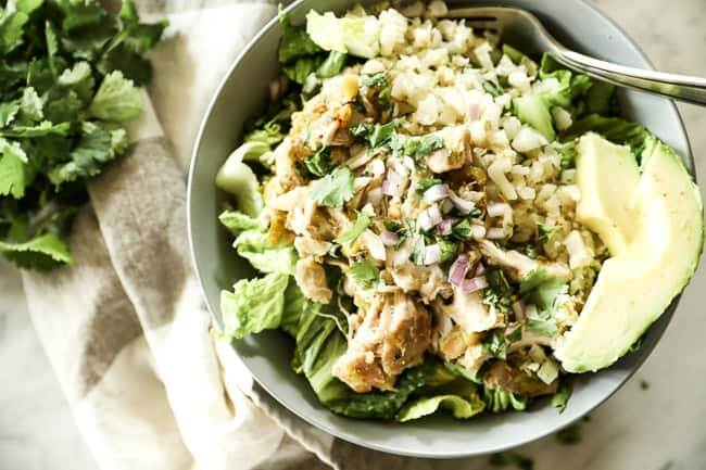 Mexican shredded chicken in a bowl with romaine lettuce, cauliflower rice and avocado. Topped chopped red onion and cilantro.