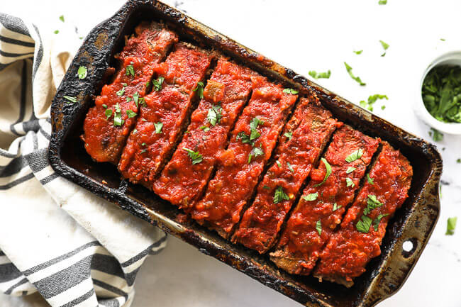 Taco meatloaf sliced in a pan with cilantro topping horizontal image